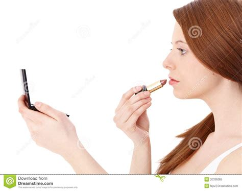 portrait of teenage girl putting lipstick on while looking at her ginger girl putting on lipstick royalty free stock photo