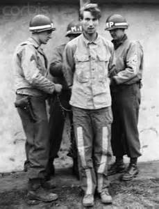 American soldiers tie one of three nazi spies to be executed to a post