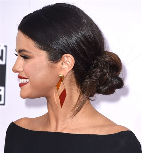 selena gomez wearing a elegant low bunchignon hairstyle here are 15 of selena gomez s best hair moments hellogiggles