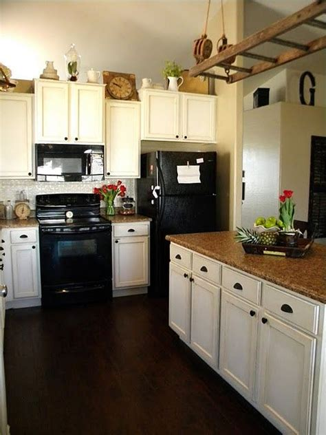 white kitchen with black appliances white cabinets with black appliances white tin backsplash dark wood floor mid range brown
