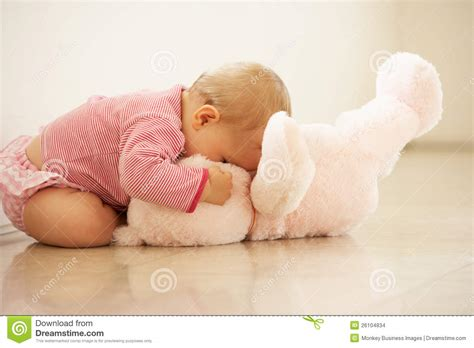 how to cuddle with a girl on the couch baby girl cuddling pink teddy bear at home stock images