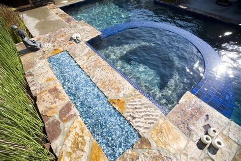 blue glass fire pit accenting the hot tub and swimming