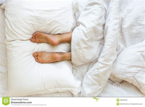 lying on my bed feet lying on soft white pillow at bed stock photo image