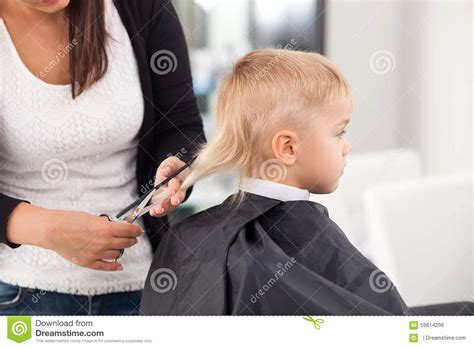 female barbershop haircut professional young hairdresser is cutting hair of stock
