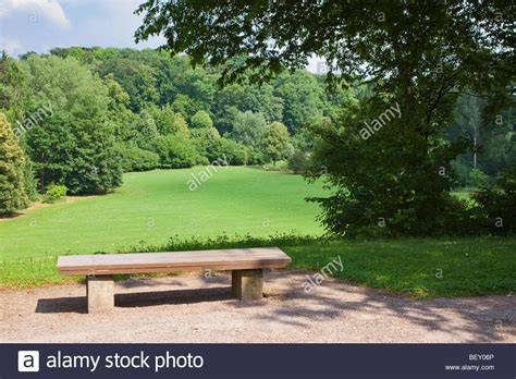 city park bench wooden park bench overlooking a field and forest in an inner city stock photo royalty