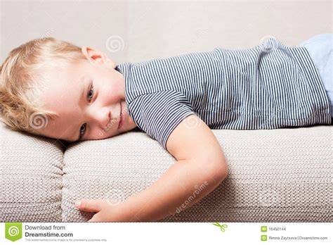 lying in the sofa little boy lying on the sofa stock images image 16450144