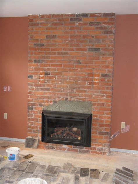 Natural stone veneer directly over existing brick fireplace Traditional Basement London