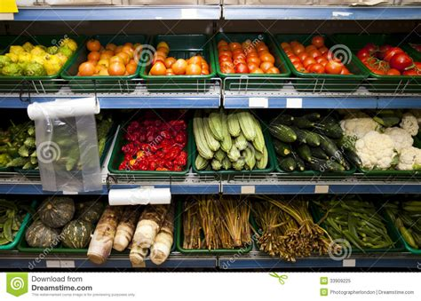 Produce Shelf by Various Vegetables On Shelves In Grocery Store Royalty