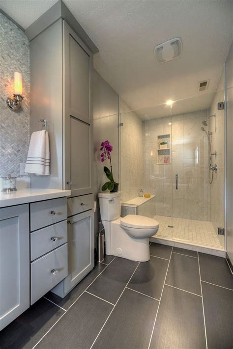 master bathroom with glass walk in shower large gray tiles on floor gray cabinets mosaic tile