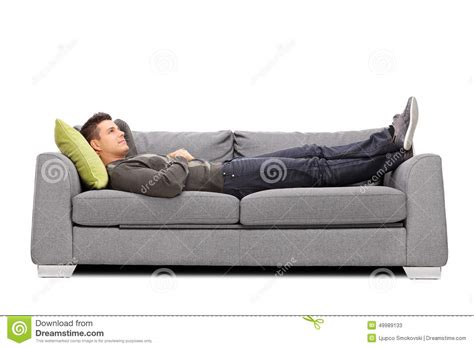 laying on couch pensive young guy laying on a sofa stock photo image
