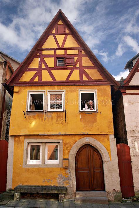 photo   yellow tudor style house    man