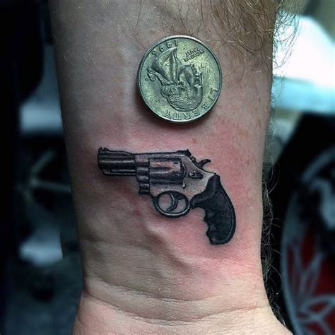 small gun tattoo with small pistol and 3d coin on wrist