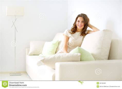 sitting on sofa smiling girl sitting on sofa stock photos image 28136483