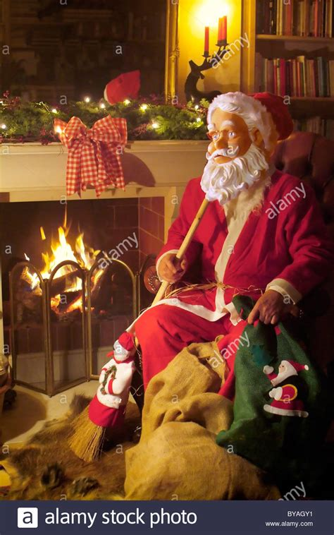 santa claus figures santa claus figure sitting in front of fireplace stock