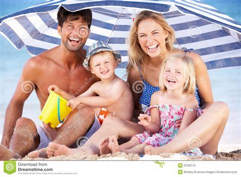 Family Nsun family sheltering from sun umbrella stock