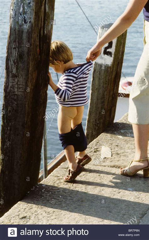 my 8 year old pees her pants during the day child mother holds on to her child as he takes a pee in the sea