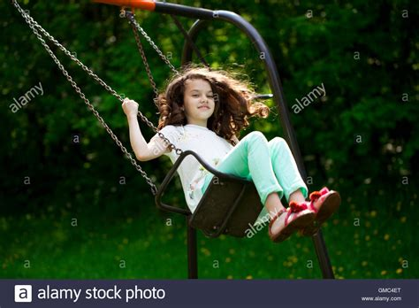 who sings swinging happy little girl on a swing in the summer park stock