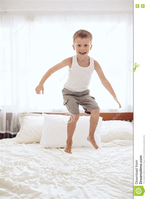 on bed boy jumping on the bed stock photo image 70400666