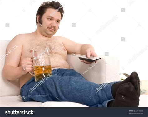 the man on the couch overweight man sitting on the couch with a beer glass and
