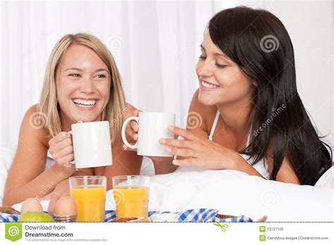 two women in bed two women having home made breakfast in white bed royalty