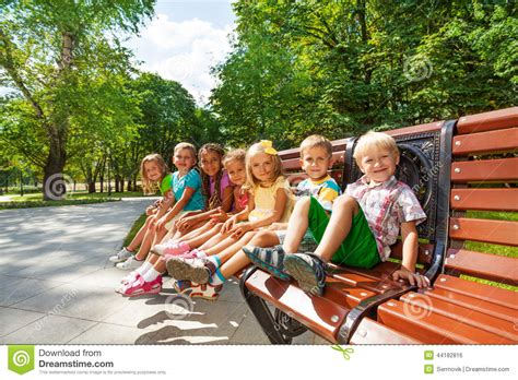 park bench group group or kids rest on bench in park stock photo image