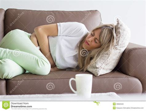 having on couch woman having stomach pain