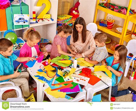 painting kindergarten children with painting on paper in