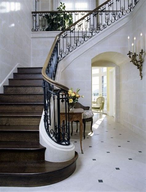 dark wood banister dark wood stairs and a wrought iron railing with brass
