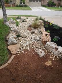 front yard landscape dry creek bed using really cool limestone boulders and accent moss