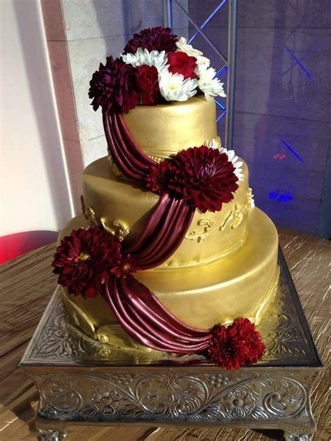 Gold cake with maroon fondant drapes.   Wedding Cakes