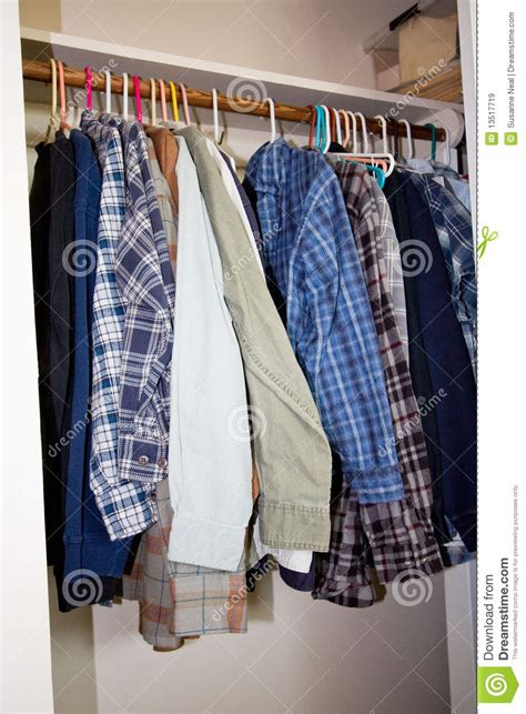 Hanging In Closet by Shirts Hanging In A Closet Royalty Free Stock Images