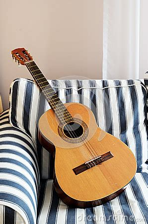 couch guitar acoustic guitar on a striped couch royalty free stock