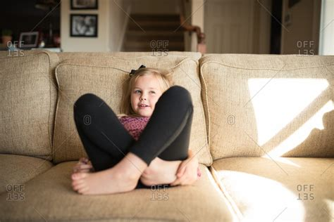 girl couch little girl sitting on a couch with her legs crossed and