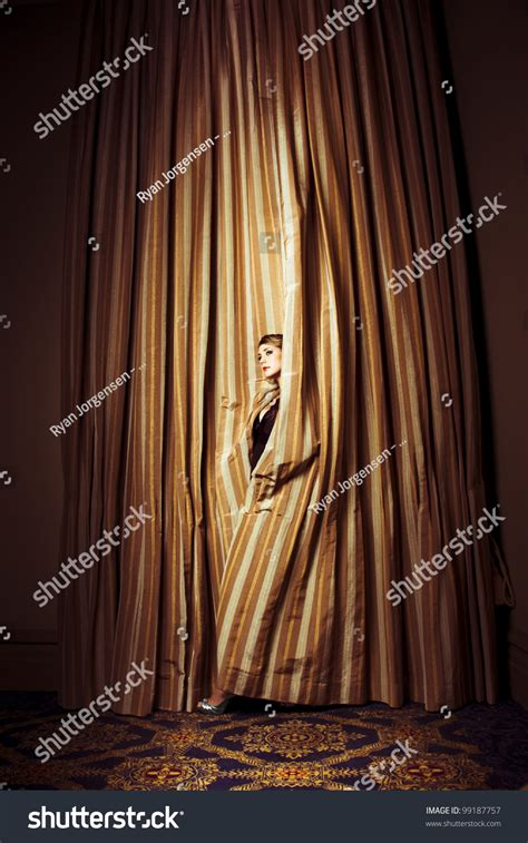 out through the curtain theatre performer peeking out through heavy gold curtains