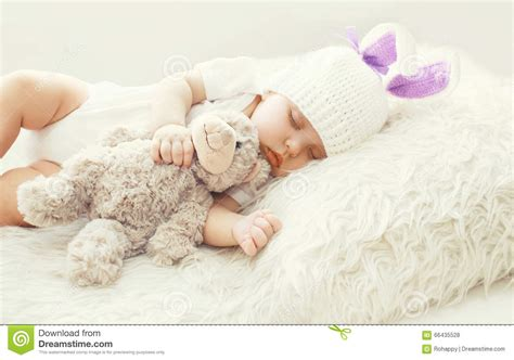 cute baby sleeping with teddy bear toy on white soft bed