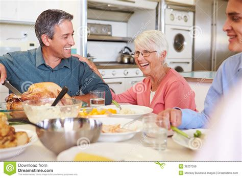 Happy In The Kitchen A Dinner A Signing by Multi Generation Family Sitting Around Table Meal