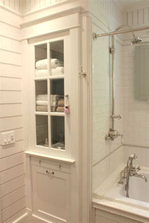 Bathroom linen cabinet and tub surround with white subway tile the inn at little pond farm