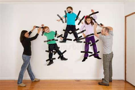for sticking pictures to walls parents sticking children to wall joke stock image image