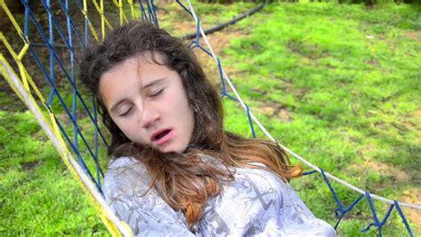 tiny petite teen model sleeping young teen girl swing and sleep in hammock yawning stock