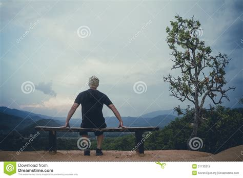 benching alone man sitting alone on bench looking at view stock image