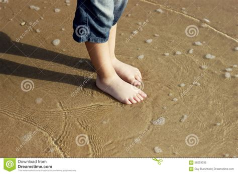 sabbia bagnata i piedi ragazzo su una sabbia bagnata fotografia stock