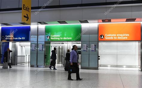 air travellers pass through customs channels at heathrow airport stock editorial photo
