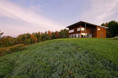modern house on the hill sits in an open meadow