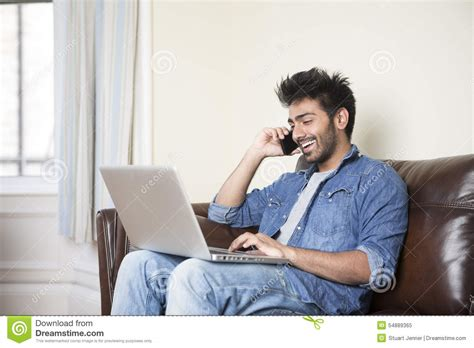indian using a laptop and phone at home stock photo