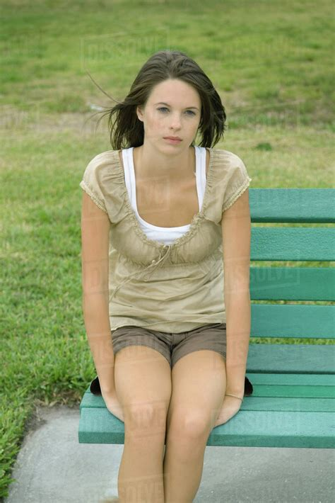 girl sitting on bench teenage girl sitting on bench looking away stock photo dissolve