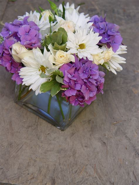 Purple Hydranges Mixed With White Roses And Daisies Make A Purple Flower Centerpiece