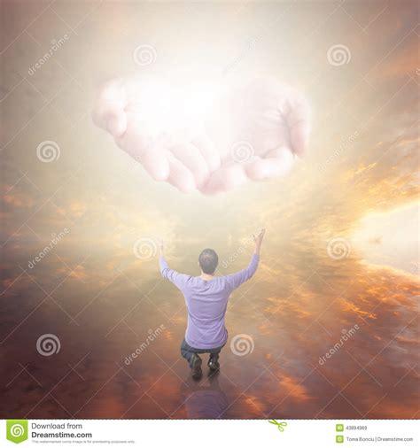 man worshiping god hands  light coming   sky stock photo image