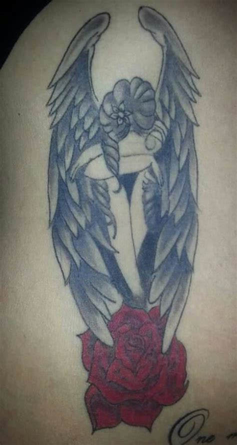 rose tattoo with angel wings and skull with wings on chest for