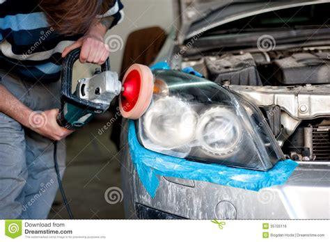 mechanic cleaning headlights and polishing with power