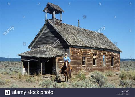 cowboy house cowboy on quarter horse outside old school house oregon usa stock photo royalty free